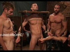 Man is bound in a medieval device, tied up and forcefully jerked off by dominati
